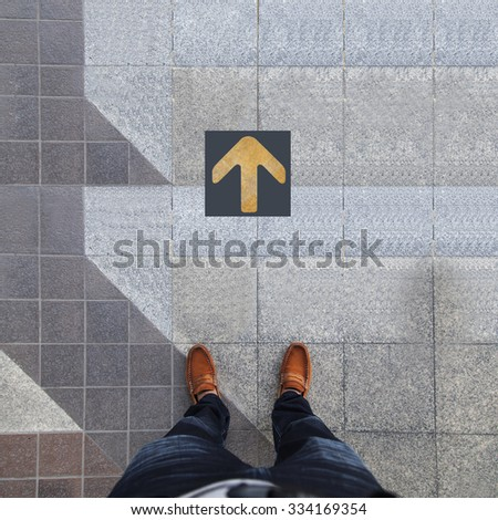Pair of shoes standing with yellow arrow - stock photo