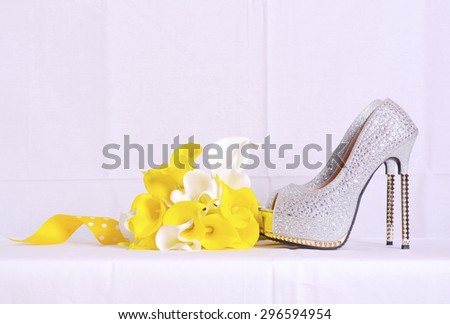 Pair of silver rhinestone high heel shoes and yellow and white arum lily bouquet on white background for wedding and bridal accessory concept.  - stock photo