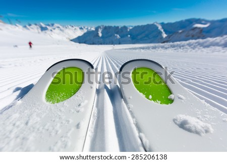 Pair of ski tips standing on the fresh snow on newly groomed  ski piste at ski resort on a sunny winter day. - stock photo