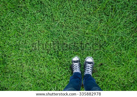 pair of sneakers black in green grass, copy space.