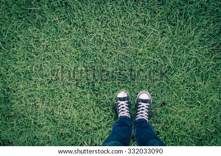 pair of sneakers black in green grass, retro style, copy space.