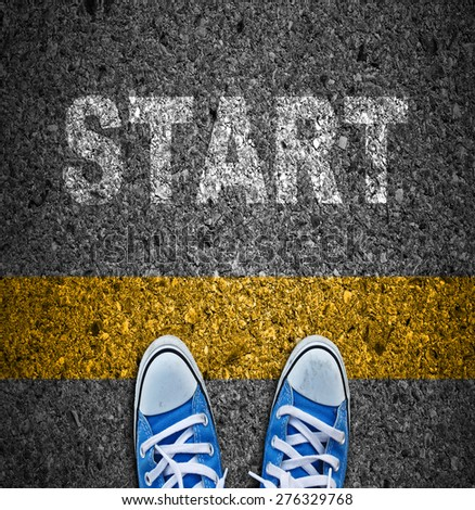 Pair of sneakers on road with yellow print of word start for the concept of starting point. - stock photo