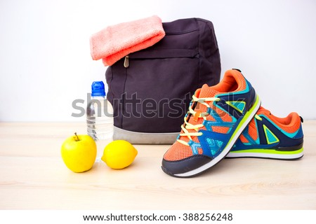Pair of sport shoes, fresh apple and accessories for fitness or sport  - stock photo