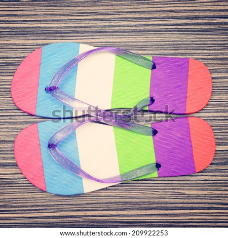 Pair of striped flip-flop sandals on wood background. Top view.