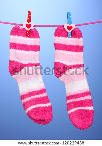 Pair of striped socks hanging to dry over blue background