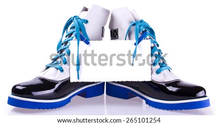 pair of stylish black and white shoes with blue laces and sole and white piece of paper attached clothespins, isolated on white - stock photo