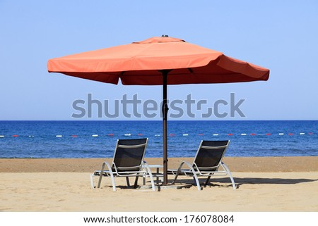 Pair of sun loungers and a beach umbrella on a deserted beach; perfect vacation concept