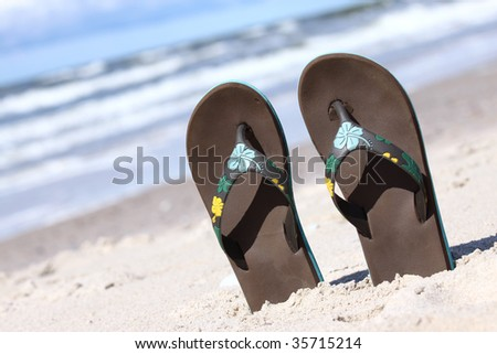Pair of thongs put in sand on the summer beach - stock photo
