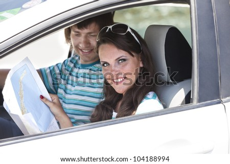 pair of travelers by the car search a route on the map. girl holds a road map - stock photo
