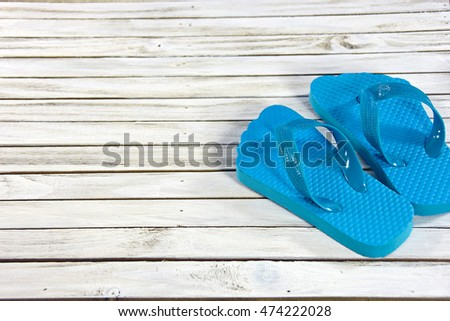 pair of turquoise flip-flops on whitewashed wooden deck