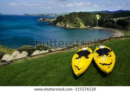 Pair of twin yellow kayaks near a wild beach. - stock photo