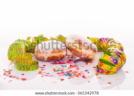 pair of two doughnuts with frosting, confetti and streamer - carnival decoration with copy space on upper section of picture - stock photo