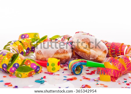 pair of two doughnuts with frosting, confetti, streamer and noisemaker - carnival decoration with copy space on upper section of picture - stock photo