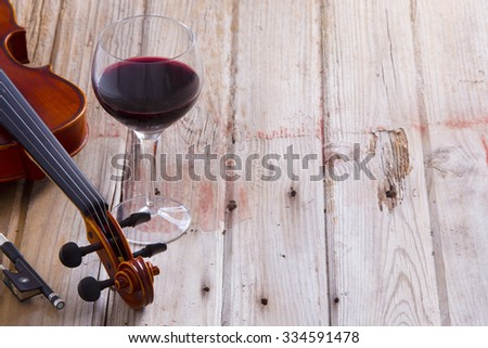 Pair of Violin Instrument and Glass of Wine Wine on a Wooden Floor with Copy Space on the Right. - stock photo