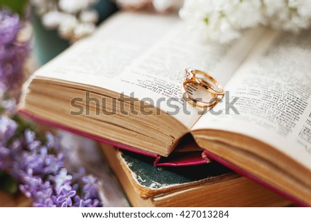 Pair of wedding rings with diamond. Rustic background with old books and lilac flowers. Retro background.