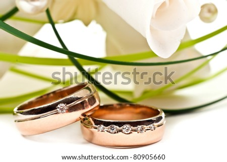 Pair of wedding rings with rose bouquet. Macro photo - stock photo