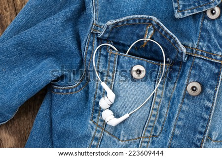 Pair of white ear-in headphones forming a heart shape in a blue pocket denim jacket - stock photo