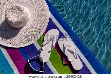 Pair of white flip flops by the pool on a bright blue, green, purple and white striped towel with sunglasses and big white floppy hat - stock photo
