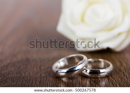 pair of white gold wedding rings on a wooden background