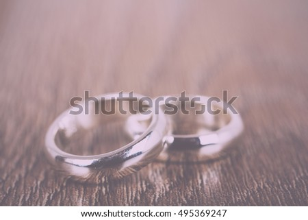 pair of white gold wedding rings on a wooden background Vintage Retro Filter.
