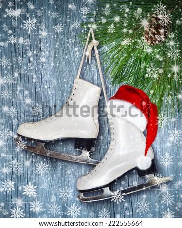 Pair of White Ice Skates and Santa Claus hat - background on vintage, retro style.  - stock photo