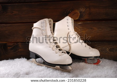 pair of white ice skates for girl on snow and wooden background - stock photo