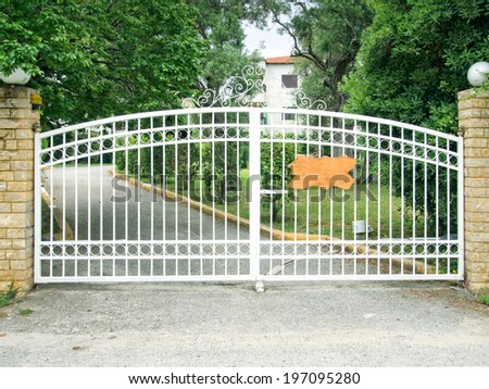 Pair of white steel gates protecting a house. - stock photo