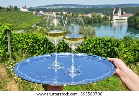 Pair of wineglasses against Rhine river and vineyards in Rheinau, Switzerland - stock photo
