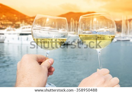 Pair of wineglasses in the hands against the yacht pier of La Spezia, Italy - stock photo