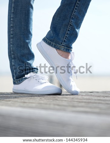 Pair of woman legs in comfortable white shoes standing outdoors