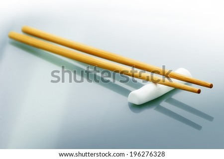 pair of wooden chopsticks on glass table - stock photo