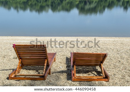 Pair of wooden deckchairs at the pebble stone beach at the bank of the Silver Lake with reflection of the trees at the water, Serbia