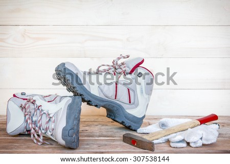 Pair of work boots with gloves and hammer on wooden background. - stock photo