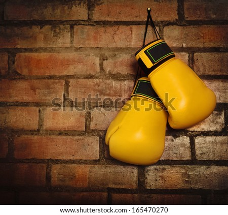 Pair of yellow boxing gloves hanging on a brick wall - stock photo