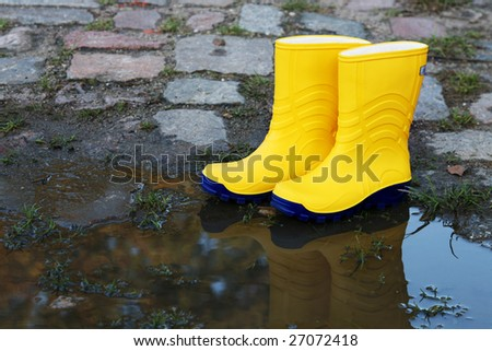 Pair of yellow rubber boots beside a puddle