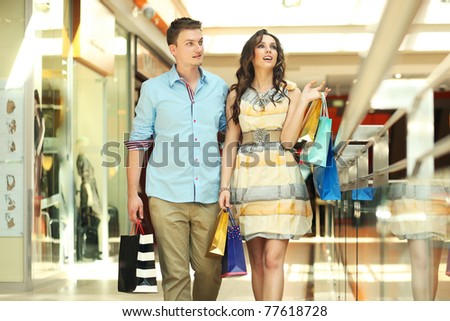 Pair of young people in shopping center - stock photo