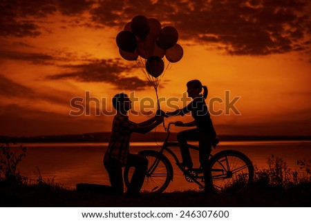 Pair on date Birthday party Silhouette of two beautiful couple Man sitting at one bicycle Woman holding give colorful balloons on sunset sky on Water in lake background Copy space for inscription