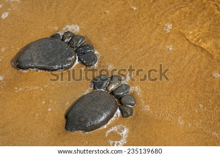 pair trace feet made of a pebble stone on the sea sand  texture surface backdrop                    - stock photo