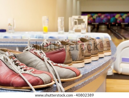 Pairs of bowling shoes lined up in shoe rack