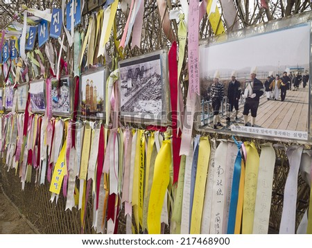 PAJU, SOUTH KOREA -MAR 27: Korean war memorial pictures and Prayer ribbons hanged on the DMZ Imjingak fence for peace and unification for North and South Korea on Mar 27, 2012 in Paju, South Korea. - stock photo
