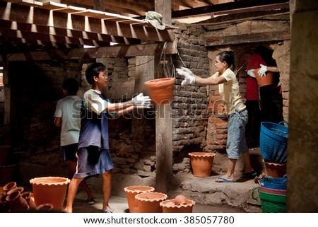 Pak Kret.Nonthaburi, Thailand - April, 26, 2015 : Workers carrying clay pots out of the kiln.