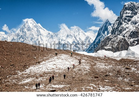 Pakistan, Baltoro Glacier, June 2015 - caravan of porters going to K2, Broad Peak and Gasherbrum's base camps. Gasherbrum IV in the background.