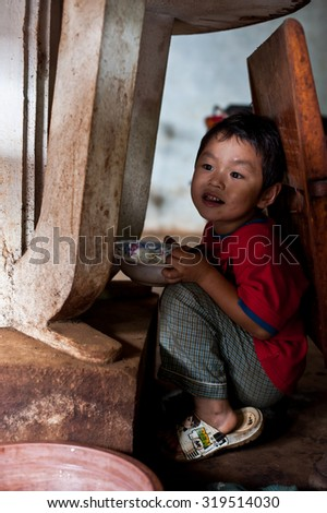 PAKSE, LAOS, August 14 : An unidentified Laos little boy sitting eating in the house of PAKSE, LAOS on August 14, 2010