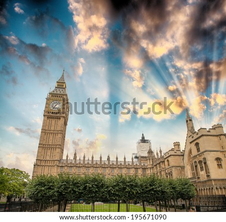 Palace of Westminster with Big Ben against a dramatic sky.