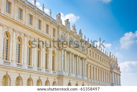 Palace side with statues on top in Versailles over blue sky. France - stock photo