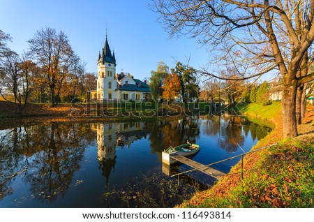 Palace with lake in a park at autumn season in Olszanica,Poland - stock photo