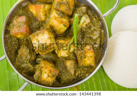 Palak Paneer - South Asian curry made with paneer (cheese) with pureed spinach sauce. Served with idlis. - stock photo