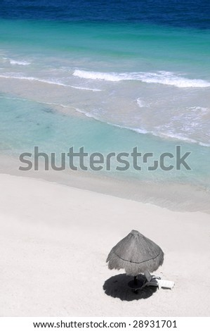 Palapa on a remote Caribbean beach with turquoise water - stock photo