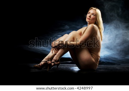Pale blond beauty naked in studio wearing jewelery