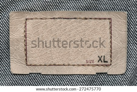 pale brown  leather label on denim background, size - stock photo